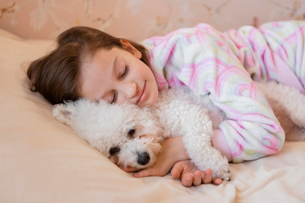 Menina abraçando o cachorro na cama enquanto dorme