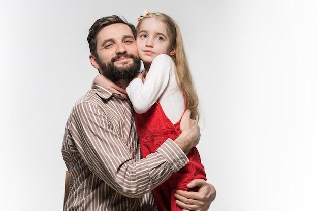 Menina abraçando o pai dela sobre um branco