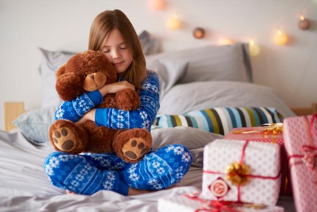 Menina abraçando o ursinho de pelúcia no natal