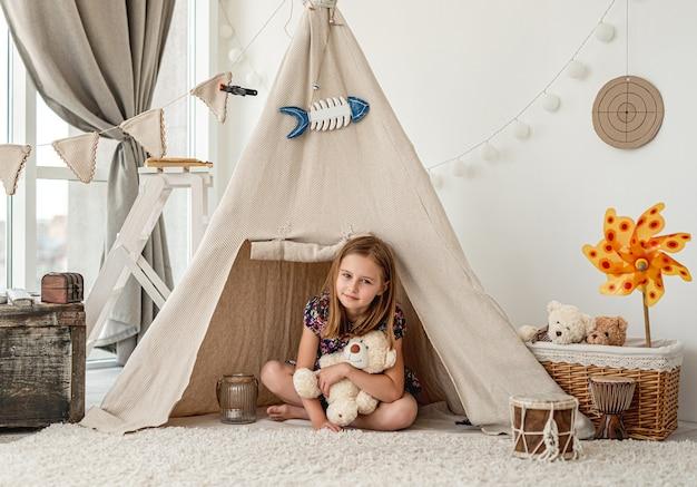 Menina abraçando o ursinho de pelúcia sentado na cabana no quarto das crianças