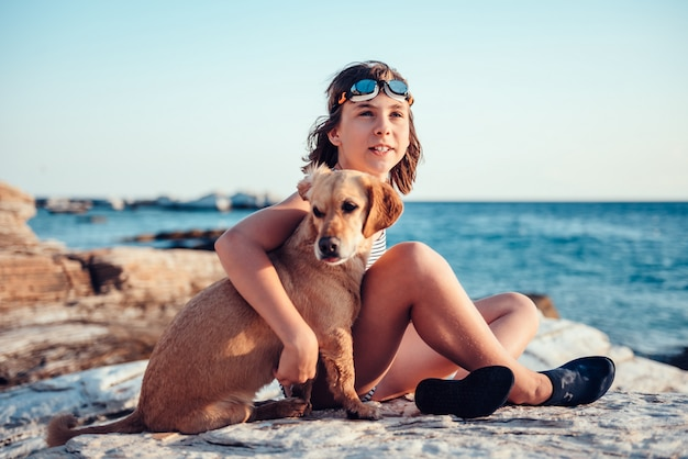 Menina abraçando seu cachorro enquanto está sentado na praia rochosa