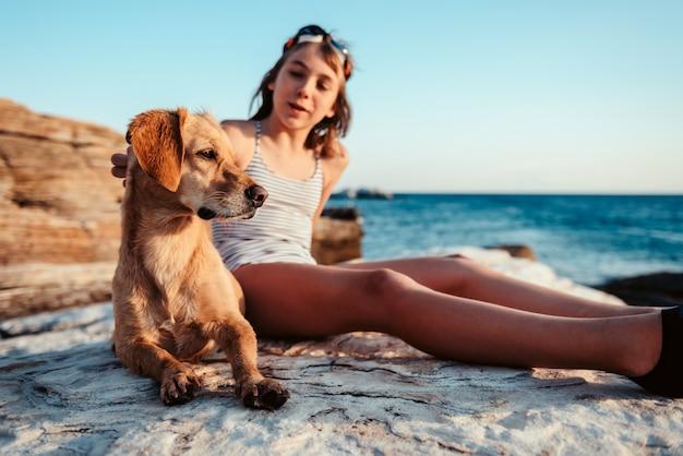 Menina abraçando seu cachorro na praia