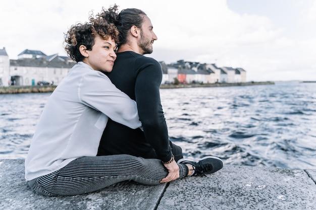Menina abraçando seu parceiro de volta com o mar fora de foco