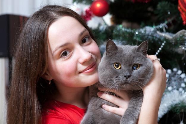 Menina abraçando um gato perto da árvore de natal