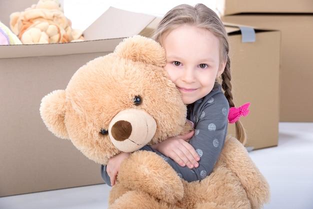 Menina abraçando um grande urso em casa e sorrindo.