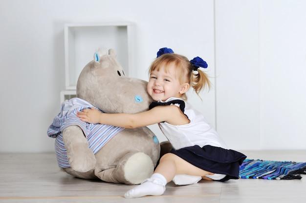 Menina abraçando um hipopótamo de pelúcia