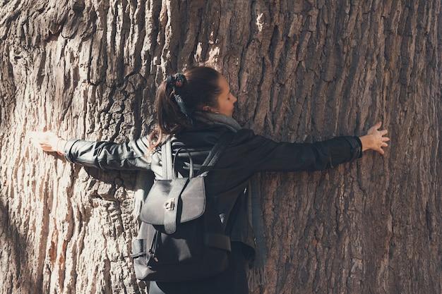 Menina abraçando uma árvore enorme. o poder das árvores. proteção da natureza, ecologia