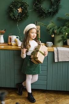 Menina abre um presente de natal na cozinha, decorada para o ano novo