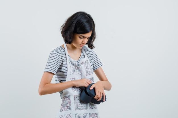 Menina abrindo a caixa de presente em t-shirt, avental e parecendo curiosa.