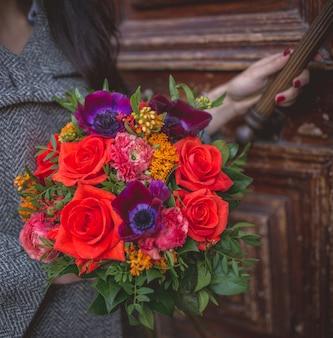 Menina abrindo a porta com um buquê de flores vermelhas e violetas.