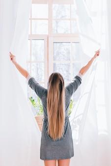 Menina, abrindo cortinas