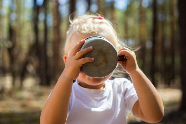 Menina acariciando o chá ou suco durante uma parada na floresta. caminhe com os pais. caminhando com os pais.