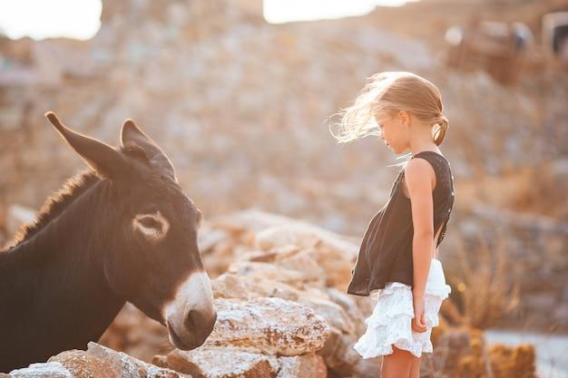 Menina acariciando um burro na ilha grega