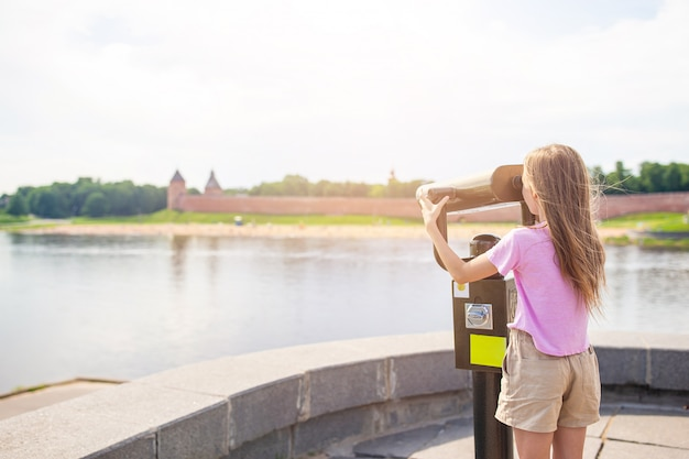 Menina admirando o kremlin de novgorod no rio volkhov