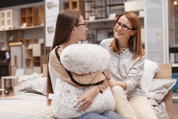 Menina adolescente abraçando uma almofada, conversando com a mãe dela no supermercado de móveis