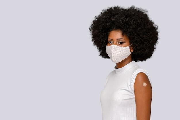 Menina adolescente afro feliz mostra a marca da vacina em um fundo cinza