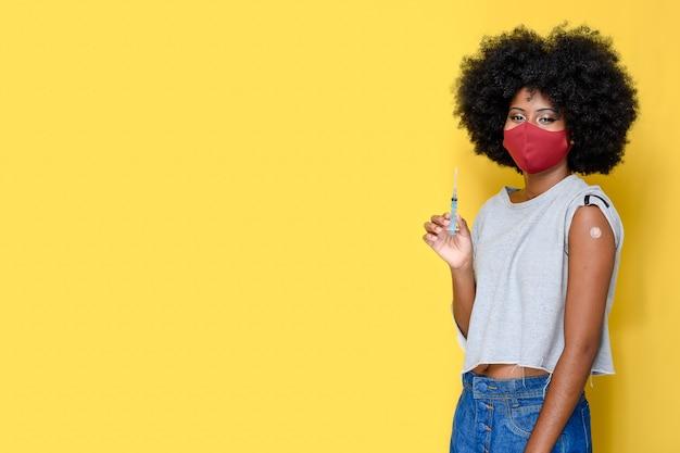 Menina adolescente afro segurando uma seringa, mostrando que foi vacinada durante a imunização de covid19