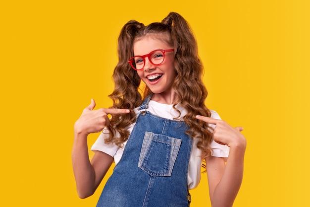 Menina adolescente alegre de macacão jeans e óculos apontando para si mesma enquanto representa a moda infantil moderna