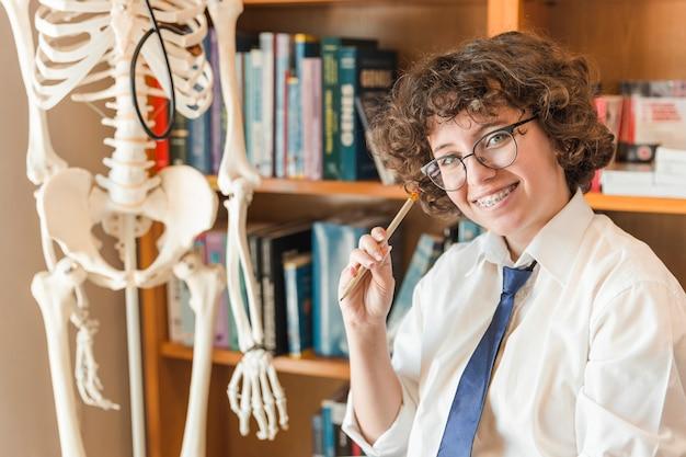 Menina adolescente alegre sentado perto do modelo de esqueleto
