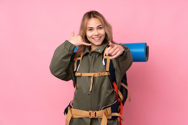 Menina adolescente alpinista com uma mochila grande isolada na parede rosa, fazendo gesto de telefone e apontando a frente