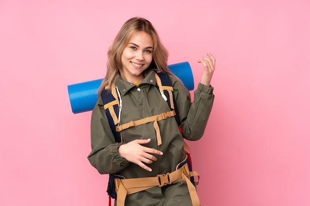 Menina adolescente alpinista com uma mochila grande na parede rosa, fazendo gesto de guitarra