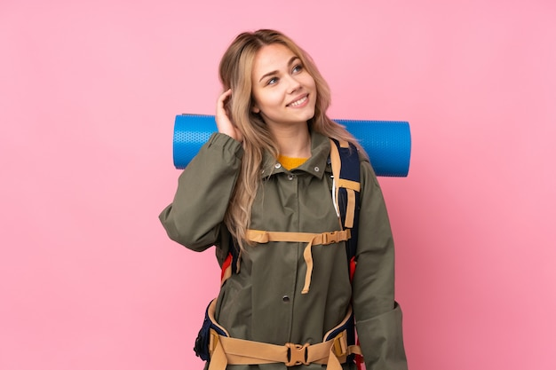 Menina adolescente alpinista com uma mochila grande na parede rosa, pensando uma idéia