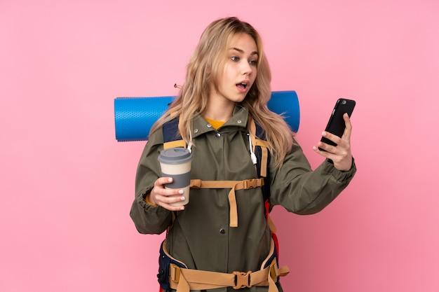 Menina adolescente alpinista com uma mochila grande na parede rosa segurando café para tirar e um celular
