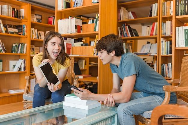 Menina adolescente animada mostrando tablet para namorado