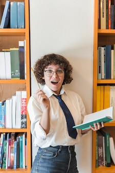 Menina adolescente animada ter ideia na biblioteca