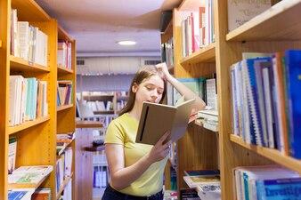 Menina adolescente, apoiando-se na estante e lendo