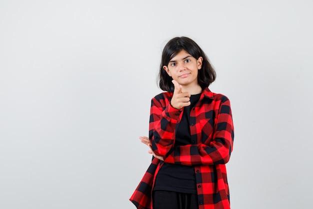 Menina adolescente apontando em uma camisa casual e olhando bem-aventurada, vista frontal.