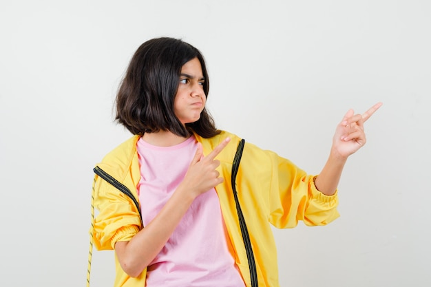 Menina adolescente apontando para cima, olhando para o lado em um agasalho amarelo, camiseta e parecendo desconfiada, vista frontal.