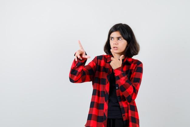 Menina adolescente apontando para longe em uma camisa casual e parecendo chocada, vista frontal.