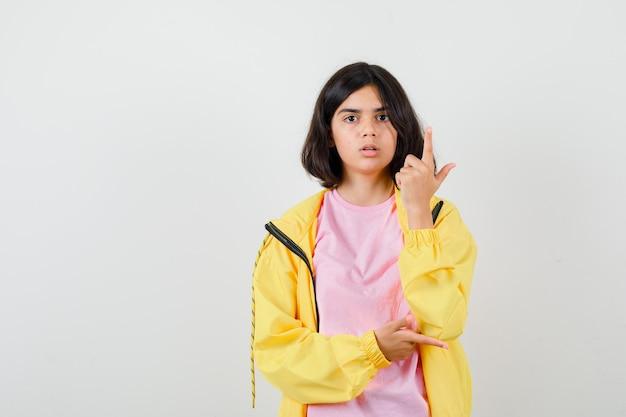 Menina adolescente apontando para o lado direito e para cima em camiseta, jaqueta e parecendo surpresa. vista frontal.