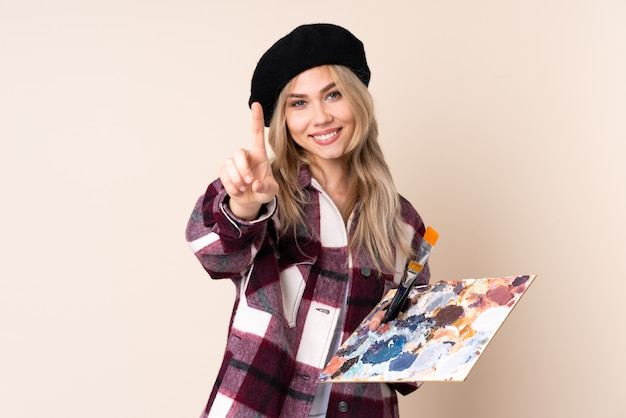 Menina adolescente artista segurando uma paleta na parede azul, mostrando e levantando um dedo