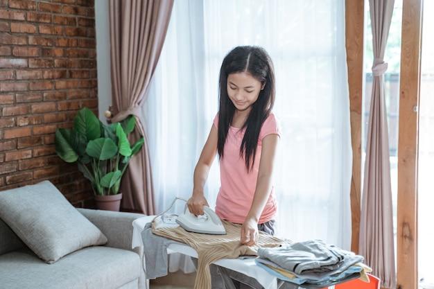 Menina adolescente asiática passando roupas para fazer a casa na tábua de passar roupa no quarto em casa