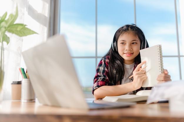 Menina adolescente asiática usando fones de ouvido, aprendendo idiomas online, usando laptop, olhando para a tela, fazendo tarefas escolares em casa, escrevendo notas, ouvindo palestras ou música, educação a distância