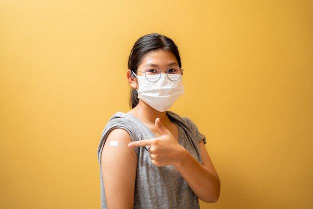 Menina adolescente asiática usando máscara protetora contra covid-19 com um sorriso no rosto mostra a marca da vacina, isolada em fundo amarelo, vacinada
