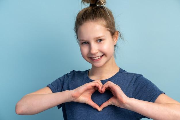 Menina adolescente atraente fazendo um coração com os dedos