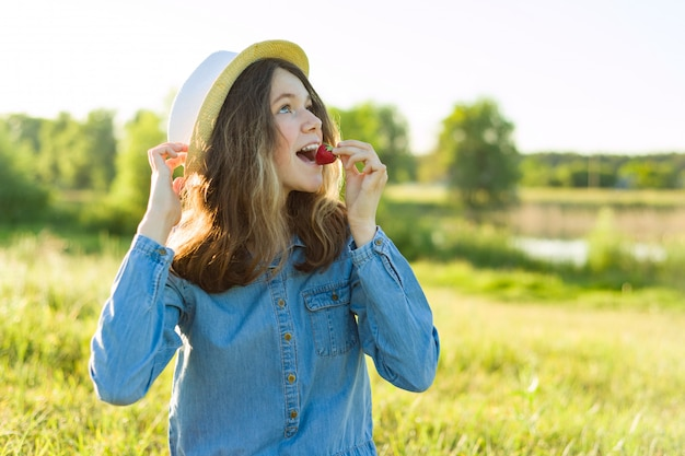 Menina adolescente atrativa que come a morango.