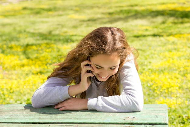 Menina adolescente bonita com smartphone celular cellfone no parque de verão
