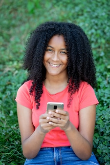 Menina adolescente bonita com um telefone móvel