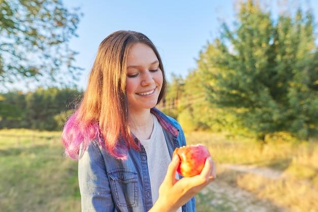 Menina adolescente bonita comendo suculenta saborosa maçã vermelha madura ao ar livre. fundo de bela paisagem natural, hora de ouro. comida natural saudável