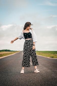 Menina adolescente bonita dançando na estrada. liberdade geração z