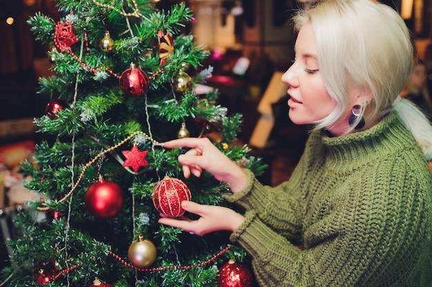 Menina adolescente bonita decorando a árvore de natal.