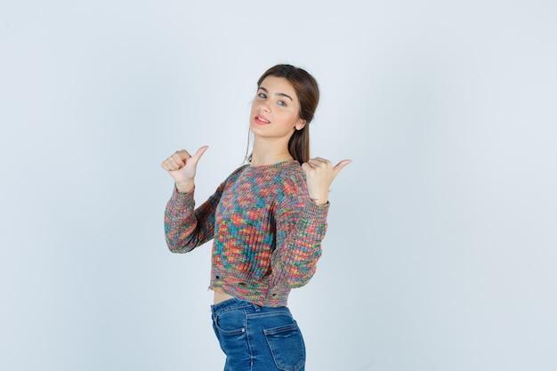 Menina adolescente bonita no suéter, jeans apontando para trás com os polegares e parecendo confiante.