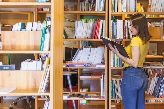 Menina adolescente bonita olhando o livro perto da estante