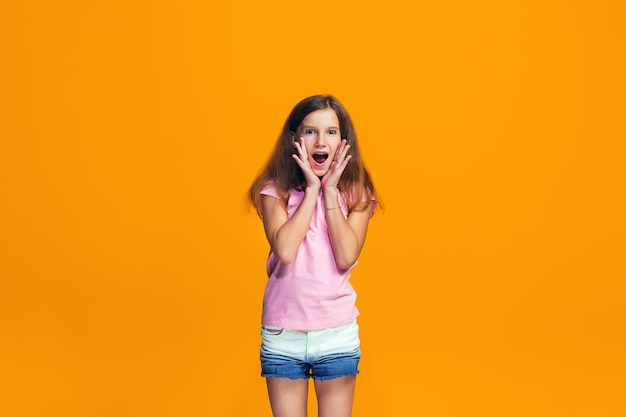 Menina adolescente bonita que olha surpreendida isolada na laranja