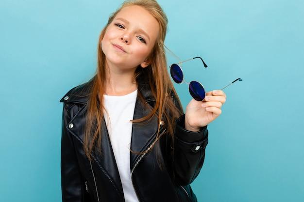 Menina adolescente bonita sobre um fundo azul com óculos de sol nas mãos
