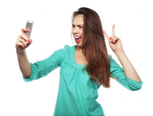 Menina adolescente bonita tomando selfies